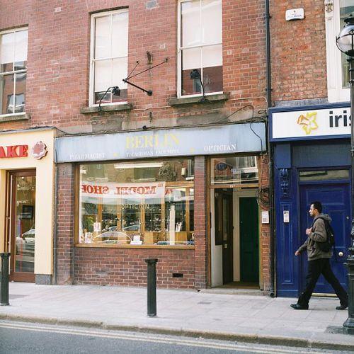 Aukščiau: optiko-žudiko Timo Kašmano parduotuvė Dubline, Capel gatvėje. Kiek žmonių pasiuntė lėtai mirčiai pasinaudodamas oftalmologijos ir optometrijos žiniomis - sunku pasakyti. Timas - tai yra viena iš pabaisų: tam kad pajusti pasitenkinimą sunaikinant kitą, nesiskaitė su jokiomis priemonėmis, taip pat ir Hipokrato priesaika. Tai Džekilas ir Haidas, kurį dėl jo veiklos bandė pridaužyti ir buvo sudaužyta jo vitriną dar 2005 m. - tuo metų, kaip pas jį užsuko savo nelaimei šio dienraščio autorius. Intuicija sakė, kad manės laukė mirtis ir su jo pasiūlyta receptūra reikėjo bėgti pas kitą optiką.